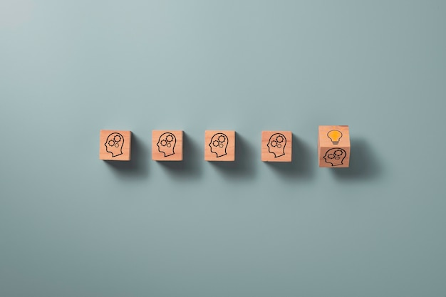 Wegklapbaar houten kubusblok dat schermgezicht met vraagteken naar gloeilamp, creatief idee en innovatieconcept afdrukt.
