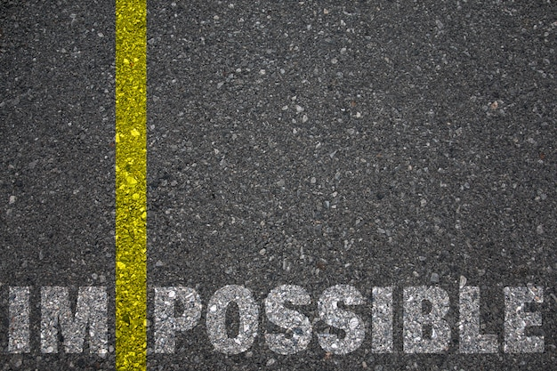 Wegmarkering gele verf scheidslijn tussen im en mogelijk als woord onmogelijk, concept afbeelding