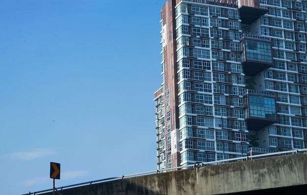 Wegweg met verkeersteken en de lange bouw op blauwe hemel in cityscape