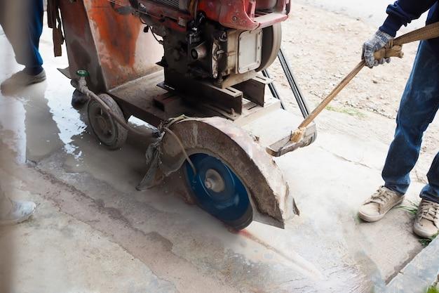 Wegwerkers snijden betonweg