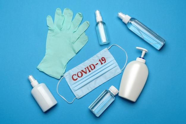 Wegwerp blauw medisch gezichtsmasker met covid-19-teken, veiligheidsbril, rubberen latexhandschoen en hoed op blauwe achtergrond