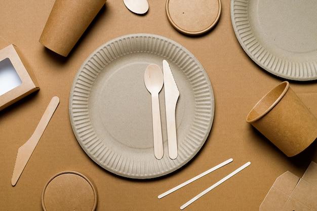 Wegwerp eco-vriendelijk servies van bamboe hout en papier op karton. de foto is bedekt met korreligheid en ruis.