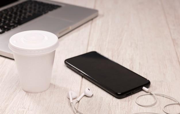 Wegwerp en recyclebare theekop met stertelefoon met oortelefoons