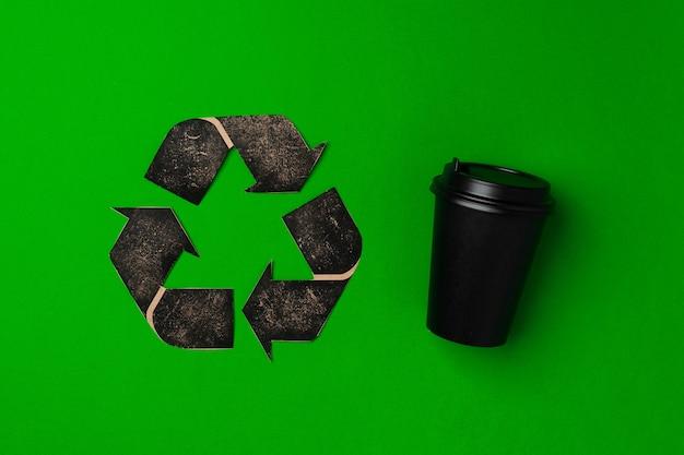 Wegwerp koffiekopje en recycling teken op groen oppervlak