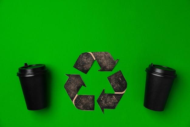 Wegwerp koffiekopje en recycling teken op groen