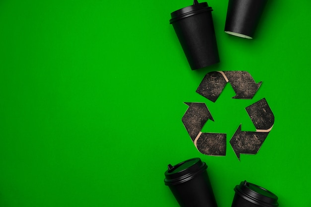 Wegwerp koffiekopje en recycling teken op groene achtergrond bovenaanzicht