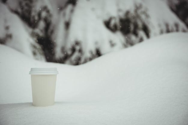 Wegwerp koffiekopje in een sneeuwlandschap
