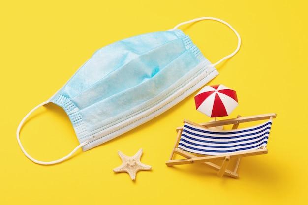 Wegwerp medisch masker zeester en speelgoed ligstoel op gele achtergrond concept van het dragen van maskers op het strand