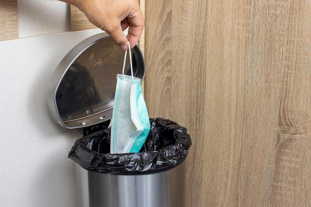 Wegwerp medische maskers in een hand die in de steek wordt gelaten in de prullenbak voor besmettelijk afval, corona-viruspreventie, covid-19-concept.
