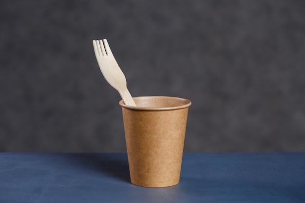 Wegwerp papieren bekers voor drankjes op een donkere achtergrond. kookgerei voor picknick eco. leeg koffiekopje bij je