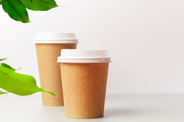 Wegwerp papieren koffiekopje en groen blad. ecologie concept