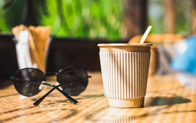 Wegwerp papieren koffiekopje met houder op tafel in café met houten roerder, in de buurt van een zonnebril. milieuvriendelijke levensstijl