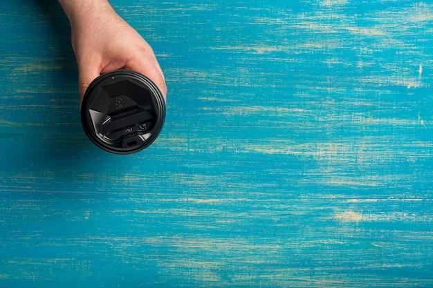 Wegwerp papieren kopje koffie in een mannenhand op blauw