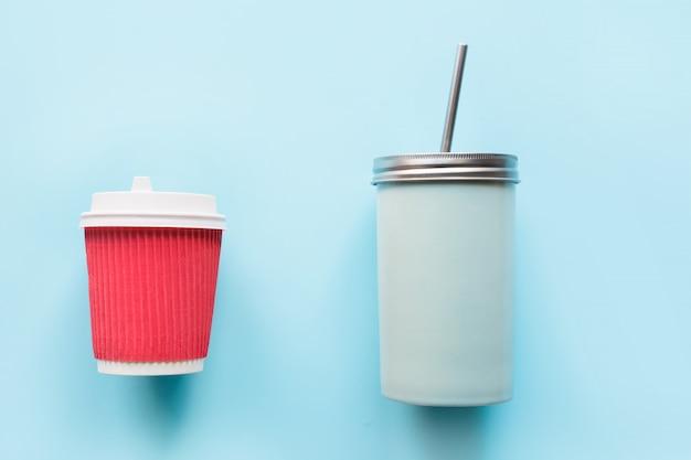 Wegwerp papieren rode beker en herbruikbare mok op blauw.