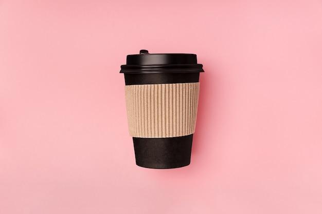Wegwerp papieren zwarte beker voor afhaalmaaltijden drink koffie die recyclebaar plat op roze achtergrondgeluid ligt