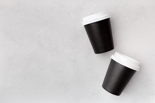 Wegwerp papieren zwarte bekers met gesloten plastic deksel voor koffie om te gaan bovenaanzicht op een grijze achtergrond met kopie ruimte.