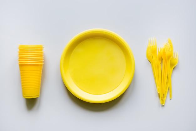 Wegwerp picknick gele gebruiksvoorwerpen, borden, kopjes, vorken op grijs.
