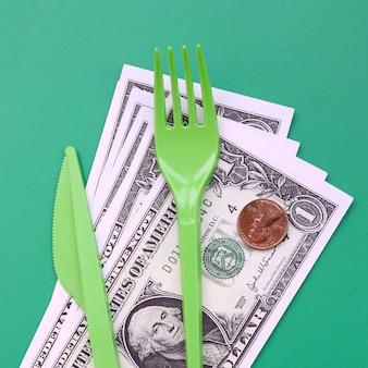Wegwerp plastic bestek groen. plastic vork en mes liggen op een klein bedrag van amerikaanse dollars