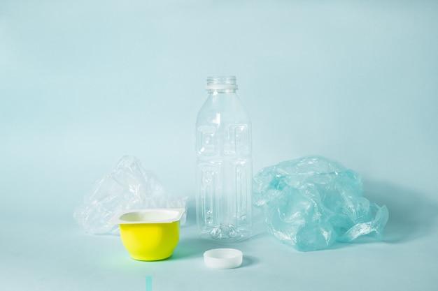 Wegwerp plastic items voor dagelijks gebruik op een blauwe ondergrond