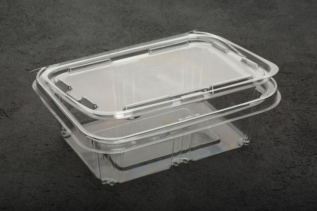 Wegwerp plastic transparante lunchbox op een zwarte betonnen tafel.