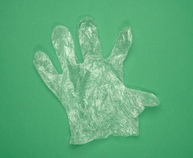 Wegwerp polyethyleen handschoen op een groene achtergrond