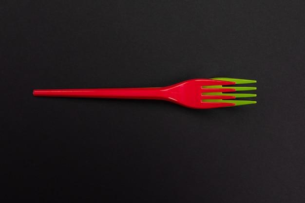 Wegwerp rode en groene plastic vorken geïsoleerd op zwart