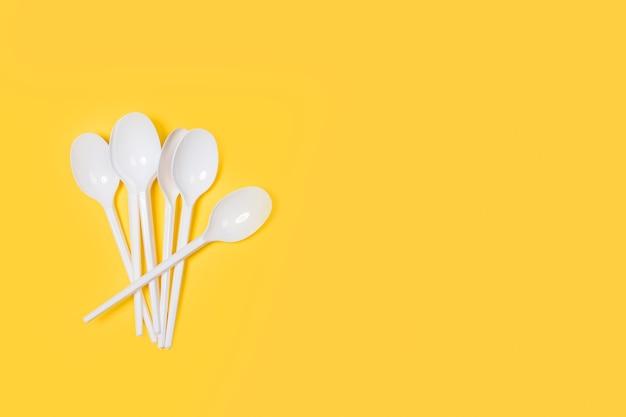 Wegwerp witte plastic lepels op een gele achtergrond in een bovenaanzicht
