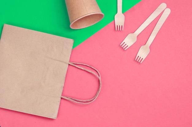 Wegwerpkeukengerei van natuurlijke materialen. eco-vriendelijk concept. houten vorken, lege ambachtelijke koffiekop, tas op groen roze