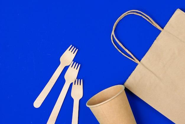 Wegwerpkeukengerei van natuurlijke materialen. eco-vriendelijk concept. houten vorken, lege ambachtelijke koffiekopje, tas op blauw