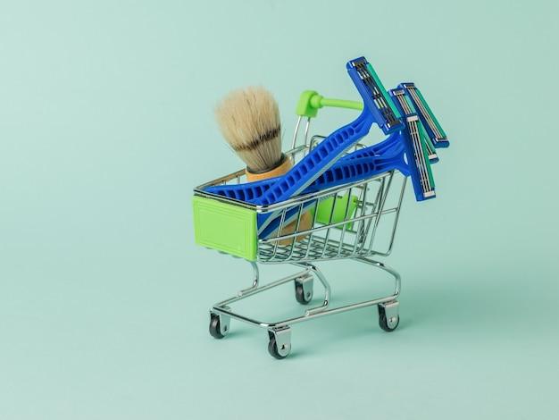 Wegwerpscheermesjes en scheerkwast in een supermarktkar op een blauw oppervlak