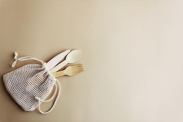 Wegwerpservies, lepel, mes en vork van natuurlijk hout in een natuurlijke stoffen zak, milieuvriendelijk.