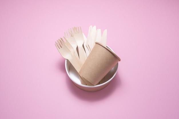 Wegwerpservies van hout en karton op een roze ondergrond