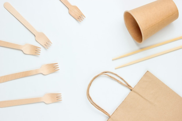 Wegwerpservies van natuurlijke materialen. eco-vriendelijk concept. houten vorken, lege ambachtelijke koffiekopje, tas, eetstokjes op een witte achtergrond.