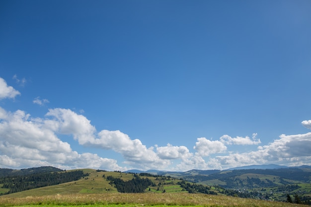 Weide, berg en blauwe lucht met wolken