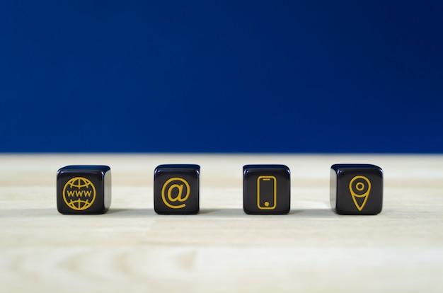Weids beeld van de klantenservice met vier zwarte dobbelstenen met gouden contactgegevens en locatiepictogrammen erop. over blauwe achtergrond.
