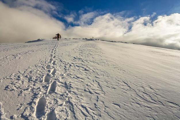 Weids uitzicht op de besneeuwde heuvel met voetafdrukken en verre wandelaar die met rugzak in de bergen naar boven loopt