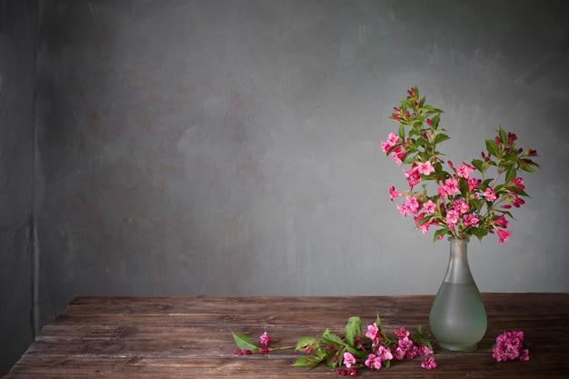 Weigela bloemen in glazen vaas op houten tafel