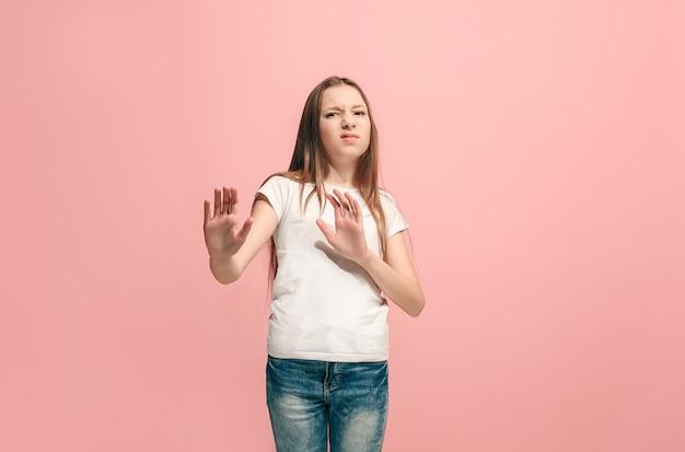 Weigeren, afwijzing, twijfel concept. jong emotioneel tienermeisje bij het afwijzen van iets tegen roze muur. menselijke emoties, gezichtsuitdrukking concept