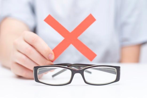 Weigering van een bril voor zicht. handen weigeren een bril. kruis op een bril. visieverbetering, laserzichtcorrectie.
