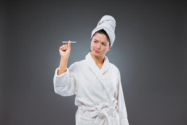 Weigering van sigaretten en tabak. een meisje met een walgelijke uitdrukking in een badjas en een handdoek om haar hoofd gewikkeld na het baden, zegt nee tegen ondeugd. gezond leven, welzijn