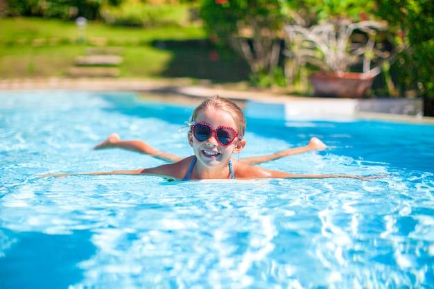 Weinig aanbiddelijk gelukkig meisje zwemt in het zwembad