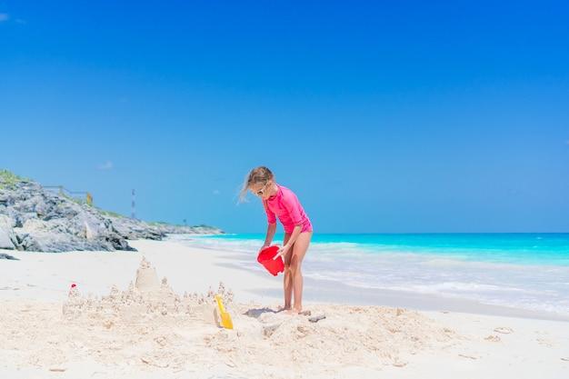 Weinig aanbiddelijk meisje dat op strand met zand speelt