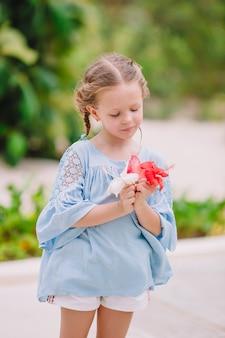 Weinig aanbiddelijk meisje die kleurrijke bloemen ruiken bij de zomerdag