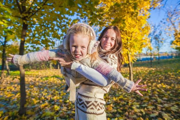 Weinig aanbiddelijk meisje en jonge moeder die pret in de herfstpark hebben op zonnige dag