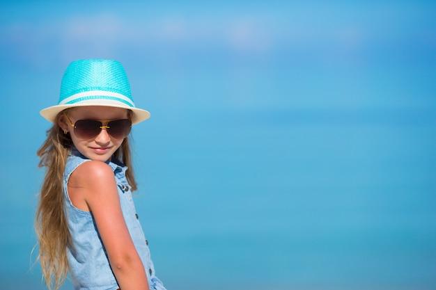 Weinig aanbiddelijk meisje in hoed bij strand tijdens de zomervakantie