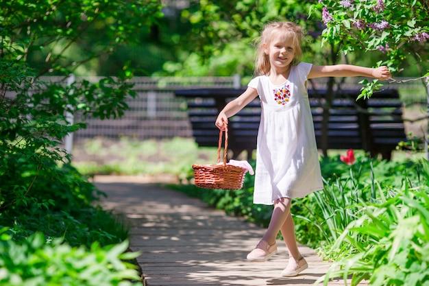 Weinig aanbiddelijk meisje met bloemen in tulpentuin