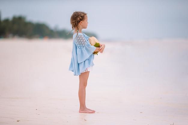 Weinig aanbiddelijk meisje met grote kokosnoot op wit zandstrand