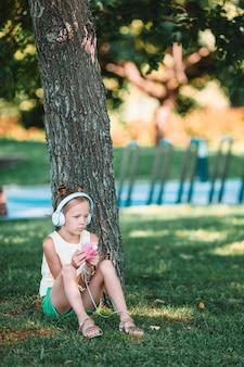 Weinig aanbiddelijke meisje het luisteren muziek in het park