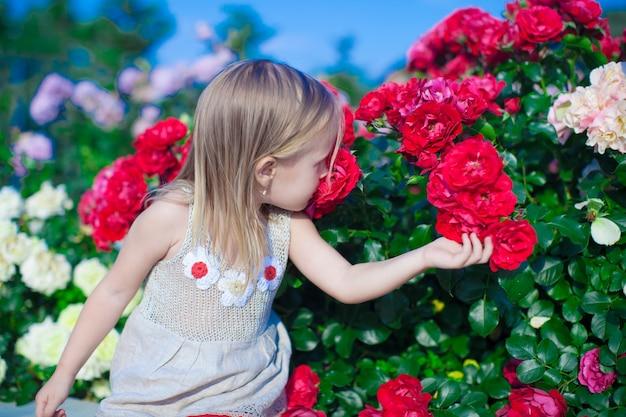 Weinig aanbiddelijke meisjeszitting dichtbij kleurrijke bloemen in de tuin