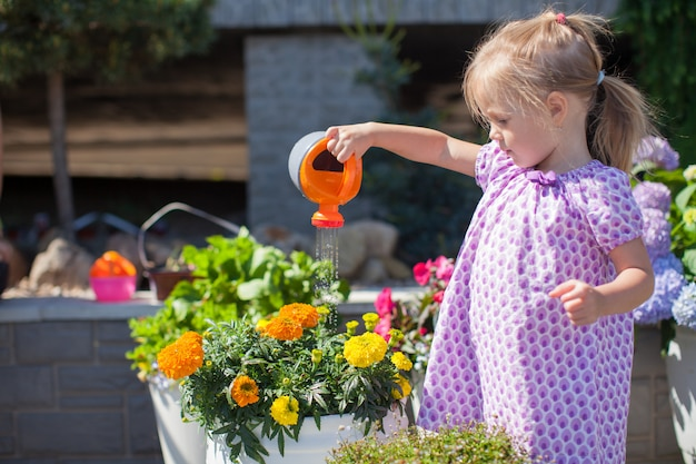 Weinig aardig meisje die bloemen met een gieter water geven